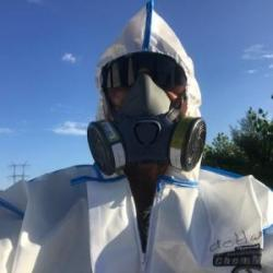 Image of Team Member Tom deHaas in personal protective gear for pesticide application